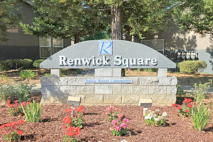 "Renwick Square stone sign, ""Senior Rental Community"" surrounded with mulch and flowers"